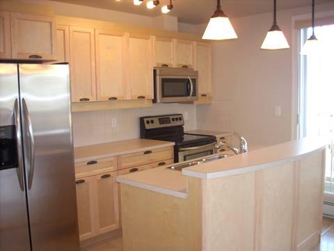 Spruce Grove Condominium. Kitchen (2 of 2): beautiful maple cabinets, patio doors lead to second balcony