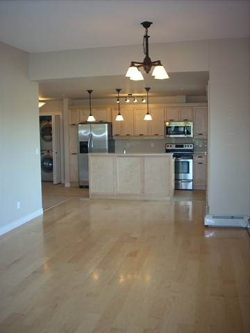 Spruce Grove Condominium. Living room to kitchen: beautiful maple floors