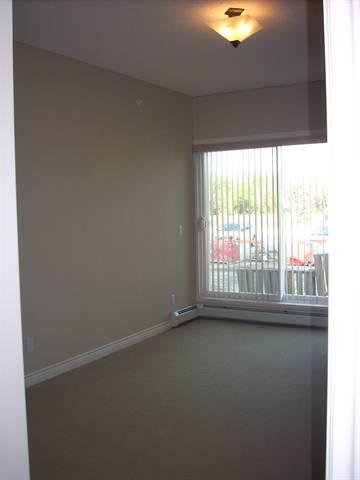 Spruce Grove Condominium. Master bedroom (1 of 2): patio doors lead to private balcony